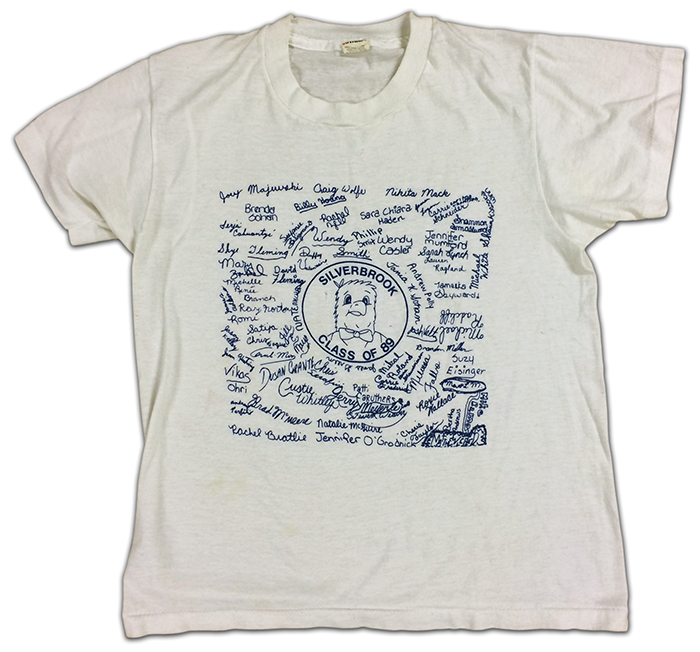 Photograph of a t-shirt given to sixth grade students in 1989. It is a white shirt with artwork in the center showing the Seahawk mascot and the signatures of all the sixth grade students.