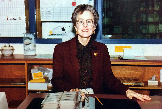 Yearbook photograph of librarian Linda Lellinger sitting at her desk.